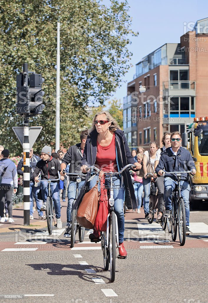 Casual dressed mature adult woman cycles in sunny Amsterdam center stock photo