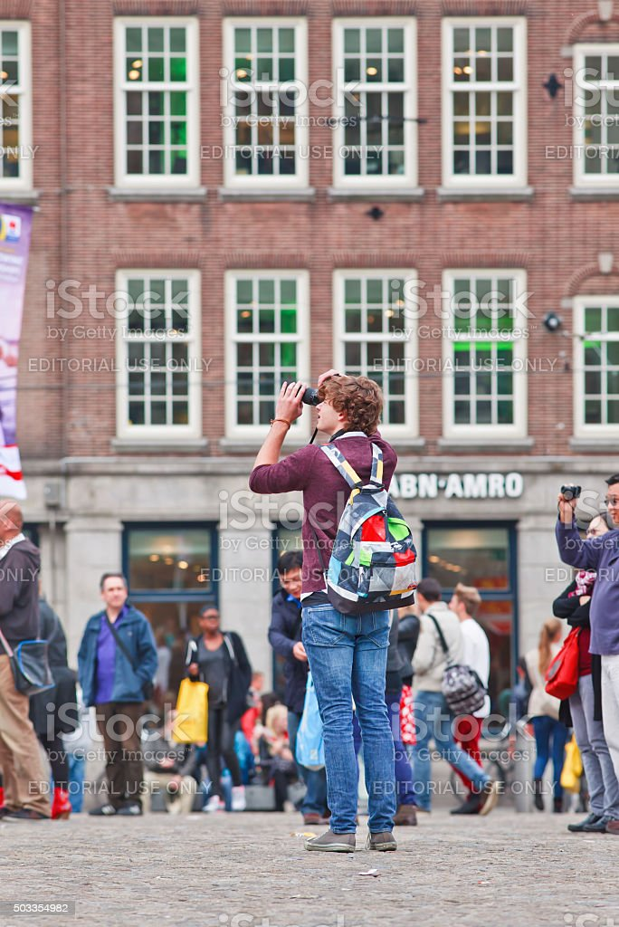 Casual dressed young man photographing on Amsterdam Dam Square stock photo