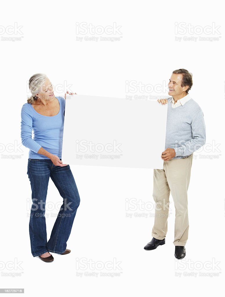 Casual elderly couple holding a blank billboard on white royalty-free stock photo