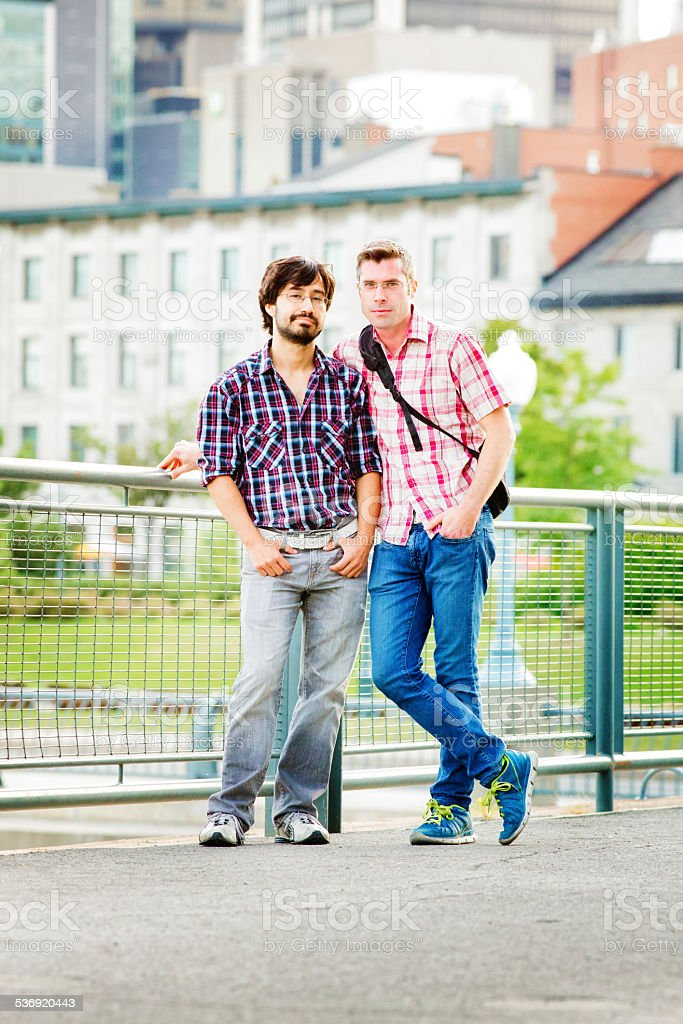 Casual gay couple in Montreal old port portrait full length stock photo