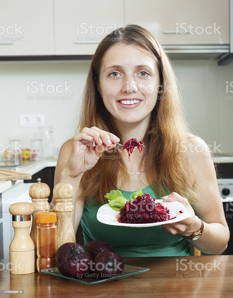 Casual  girl in green eating boiled beets royalty-free stock photo