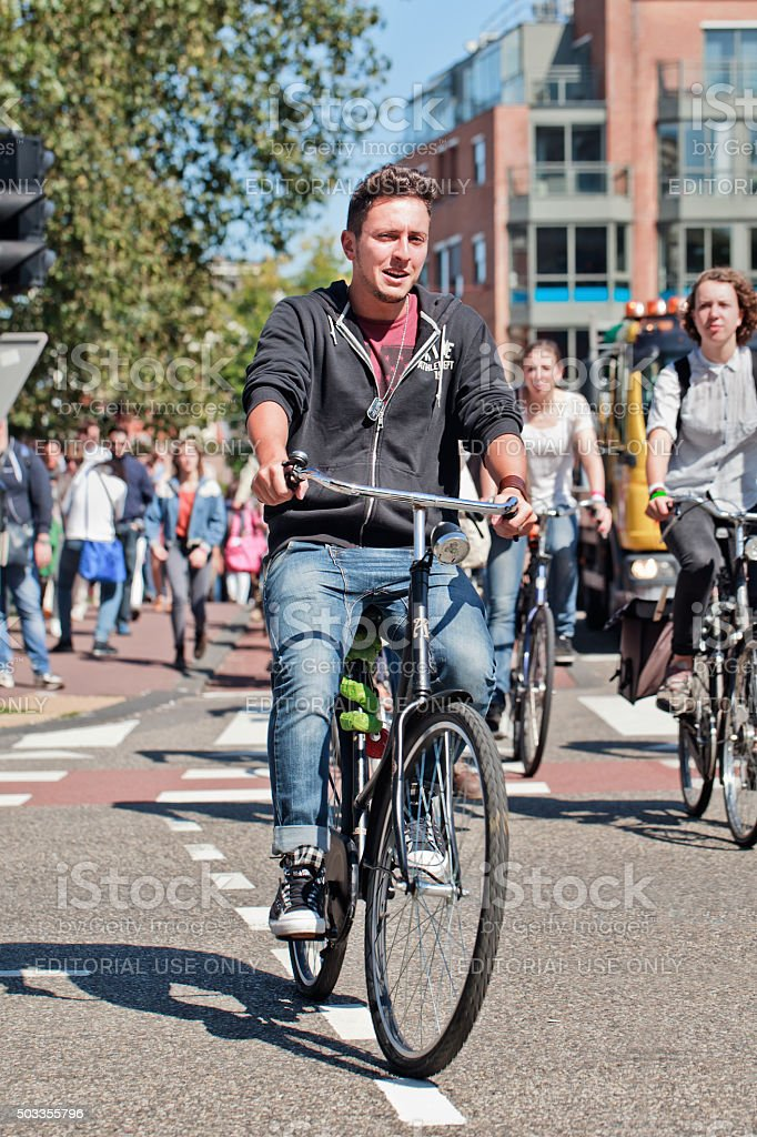 Casual handsome young man cycling in sunny Amsterdam center stock photo