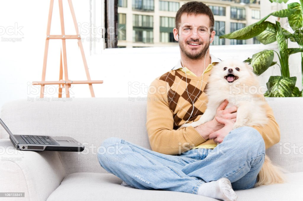 Casual Man at Home with Laptop Computer & Pomeranian royalty-free stock photo