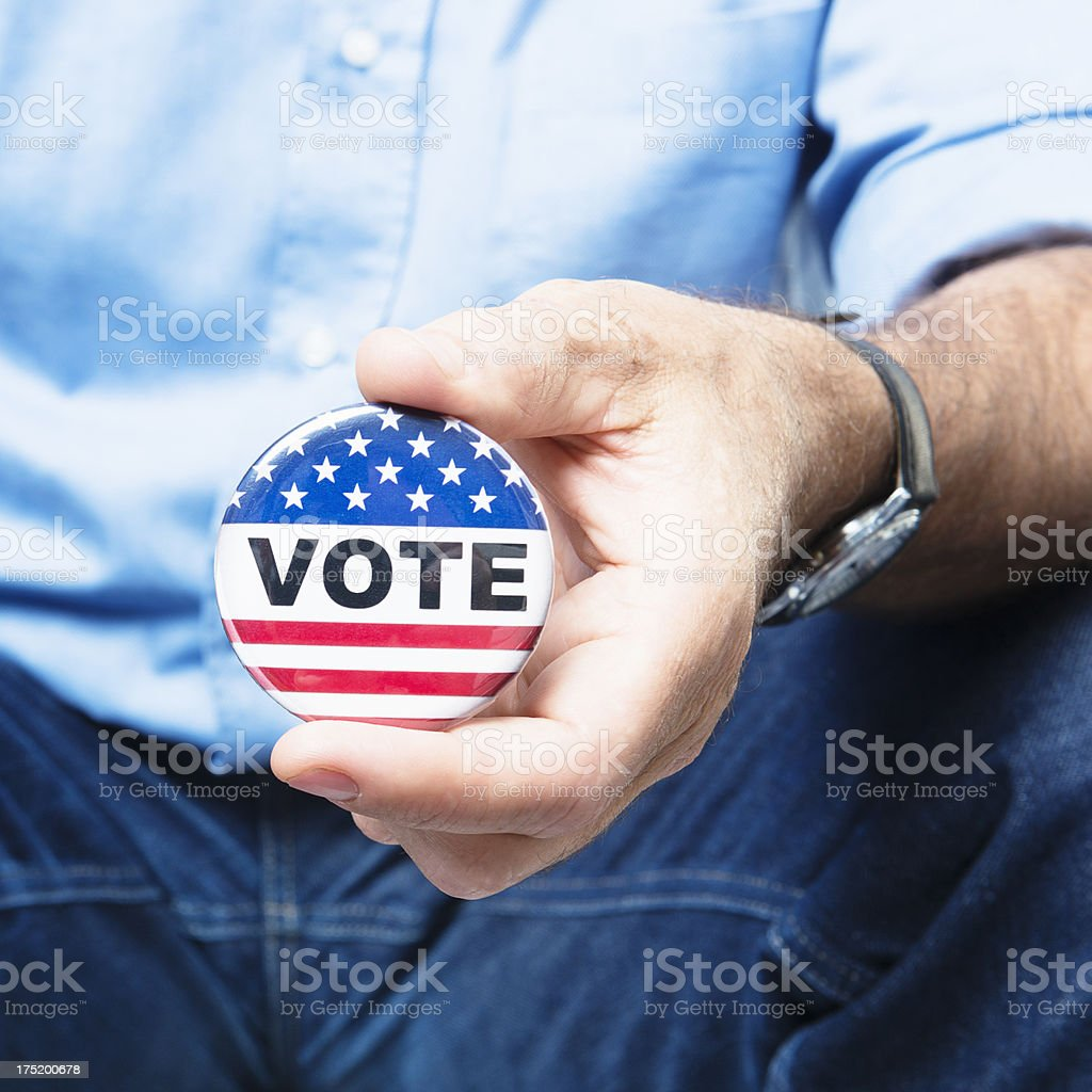 Casual man holding a vote button for the election royalty-free stock photo