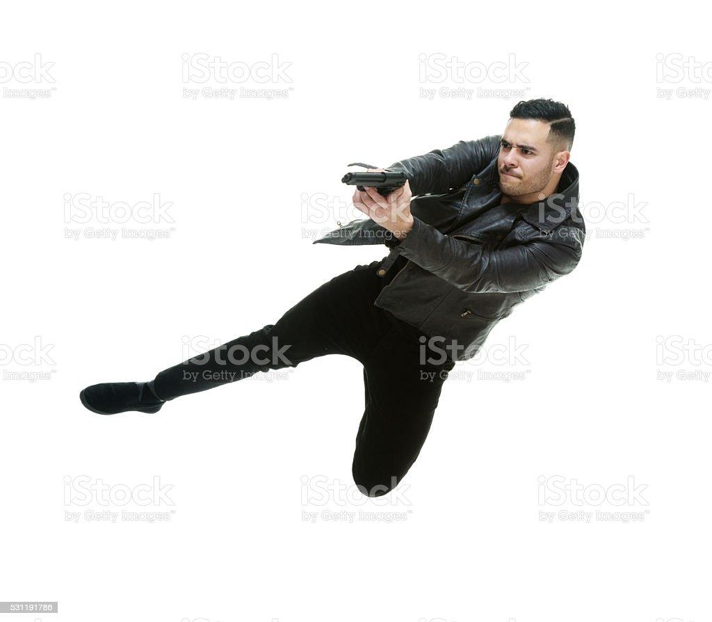 Casual man jumping with handgun stock photo