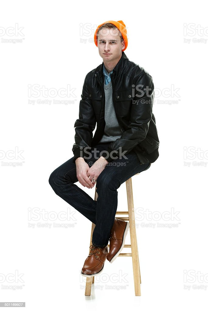Casual man sitting on stool & looking at camera royalty-free stock photo
