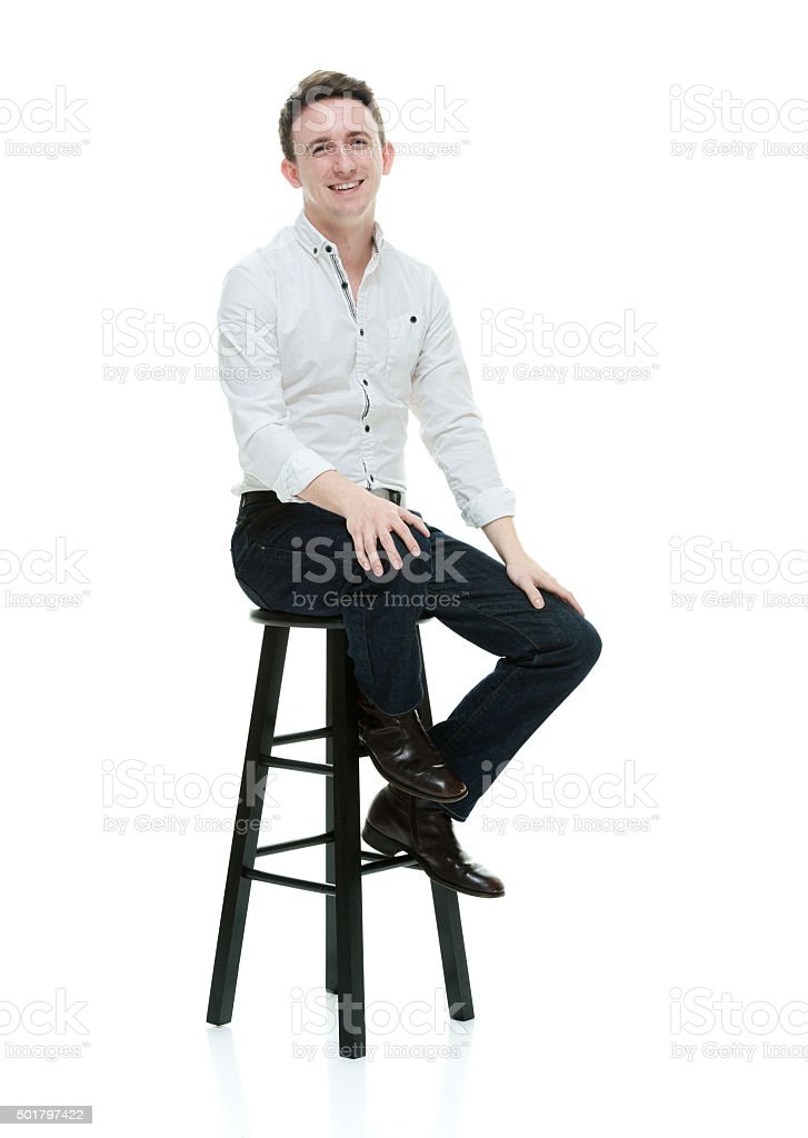 Casual man sitting on stool stock photo