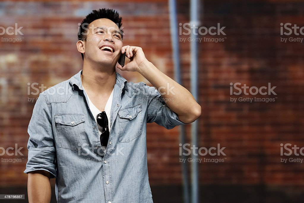 Casual man talking on mobile in front of wall stock photo