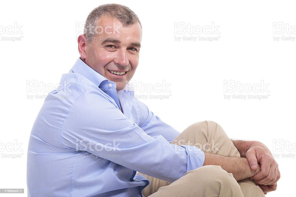 casual old man sits and smiles at you royalty-free stock photo