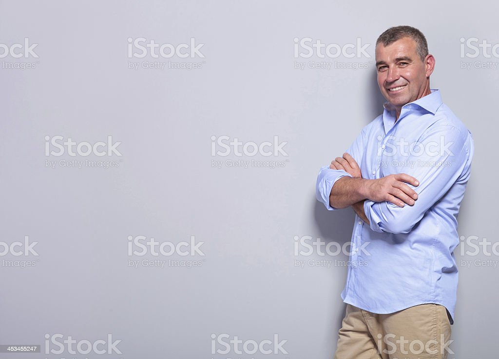 casual old man with arms crossed on gray royalty-free stock photo