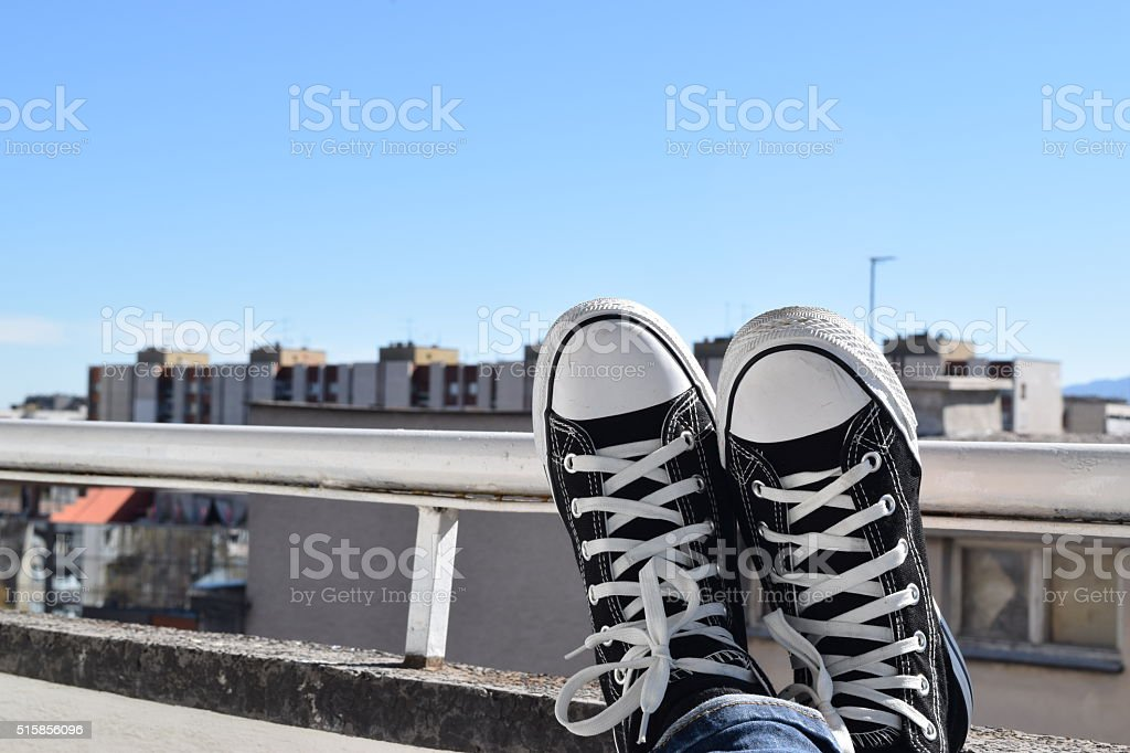 Casual shoes with legs crossed stock photo