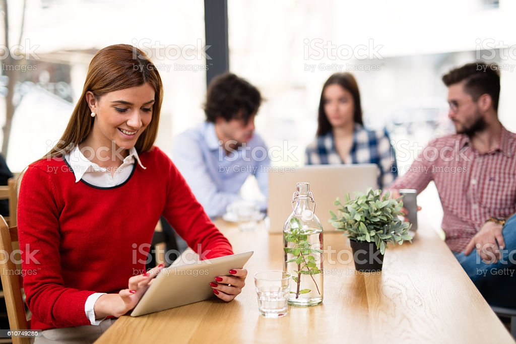Casual smiling business woman using digital tablet in cafe. stock photo