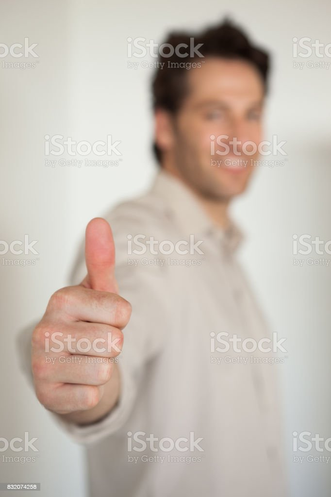 Casual smiling businessman showing thumbs up to camera stock photo