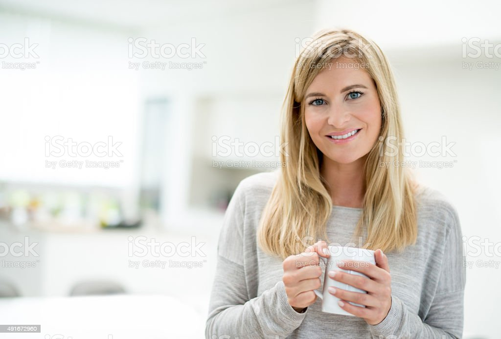 Casual woman at home drinking coffee stock photo