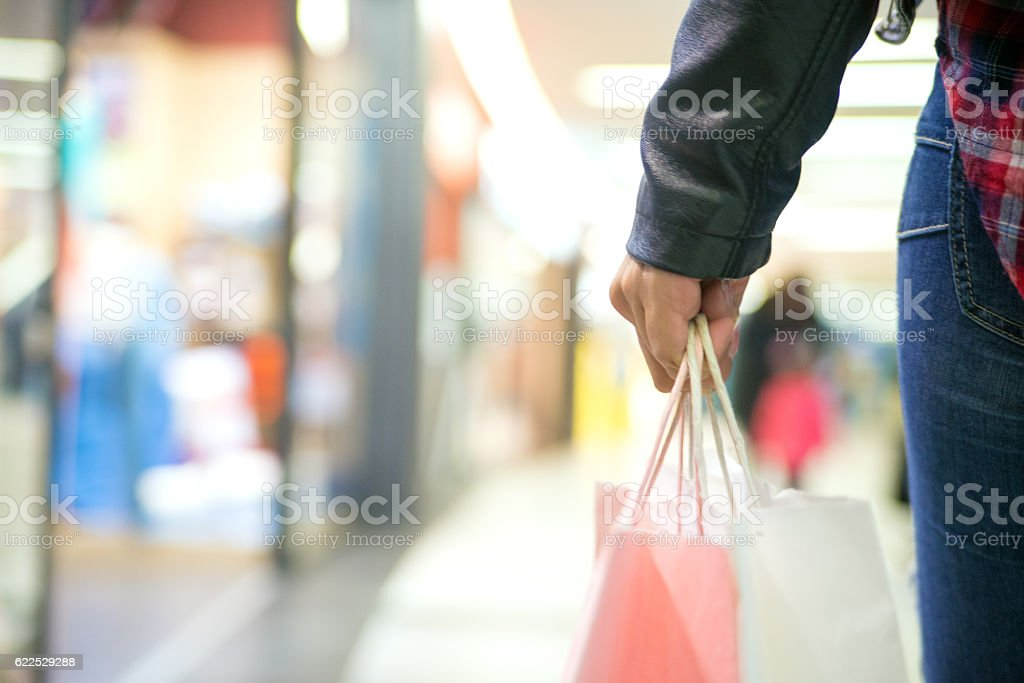 Casual woman carrying shopping bags in a mall stock photo