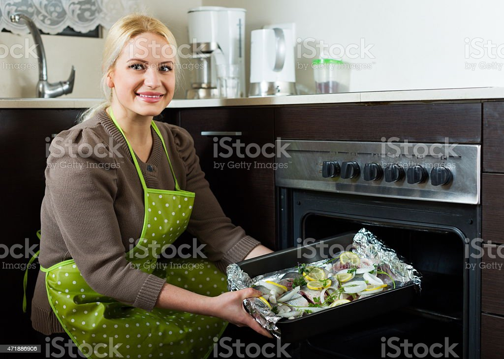 Casual woman cooking fish stock photo