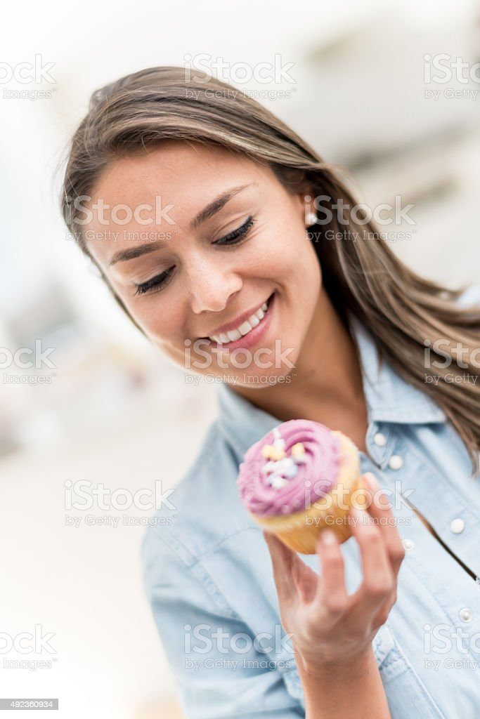Casual woman eating a cupcake stock photo