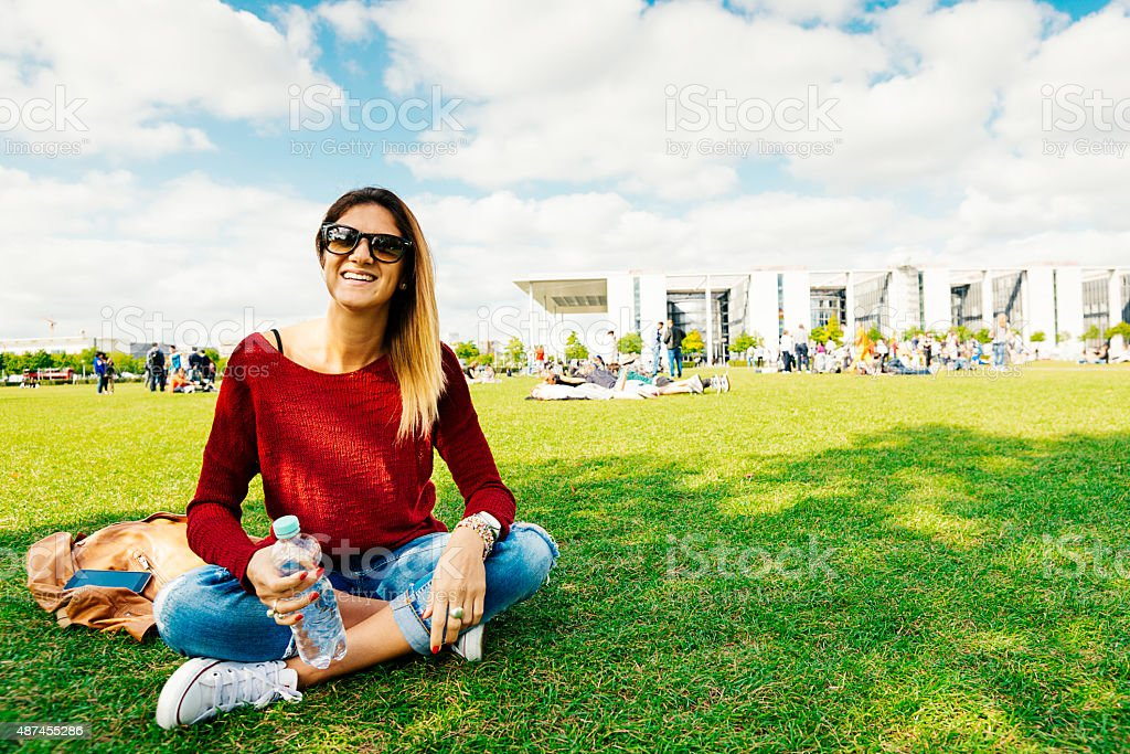 Casual woman sitting in park with water bottle and smiling stock photo