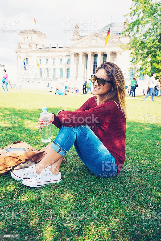 Casual woman sitting on field near German Parliament in Berlin stock photo