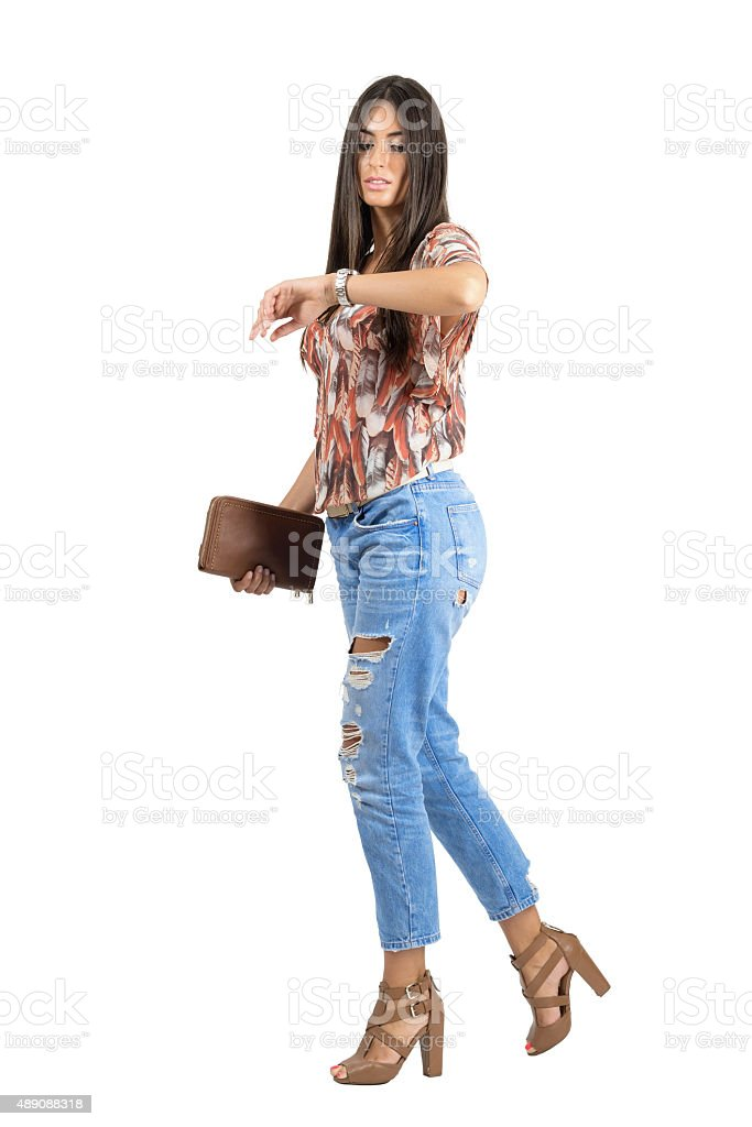 Casual woman walking and checking time on hand watch stock photo