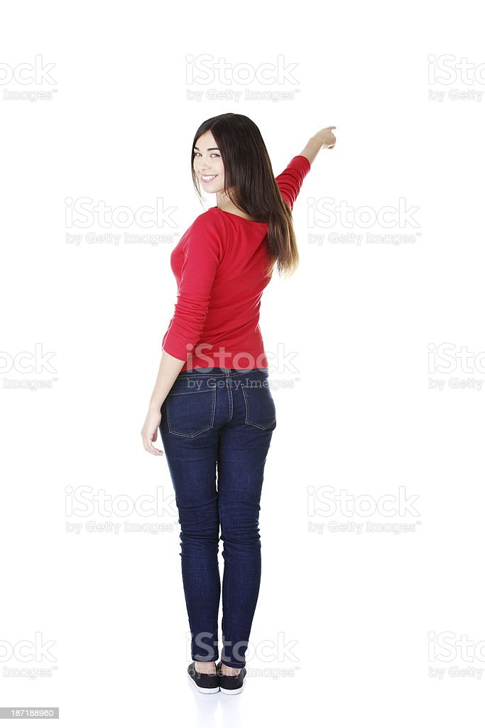 Casual women in red tshirt pointing up. Back view. royalty-free stock photo