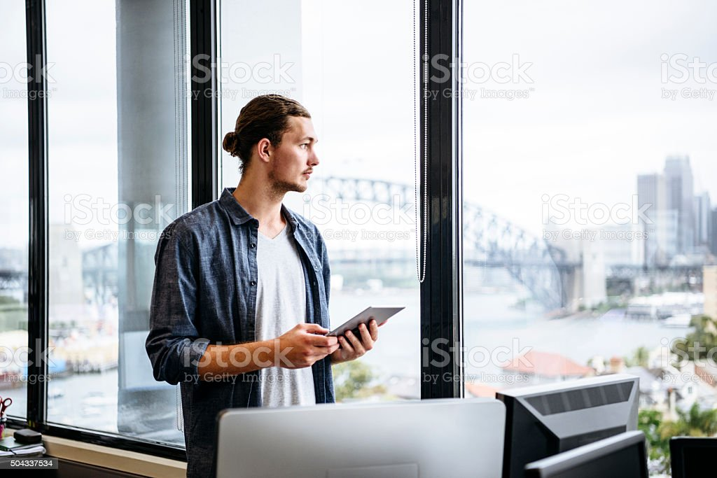 Casual young businessman with tablet by window in modern office stock photo