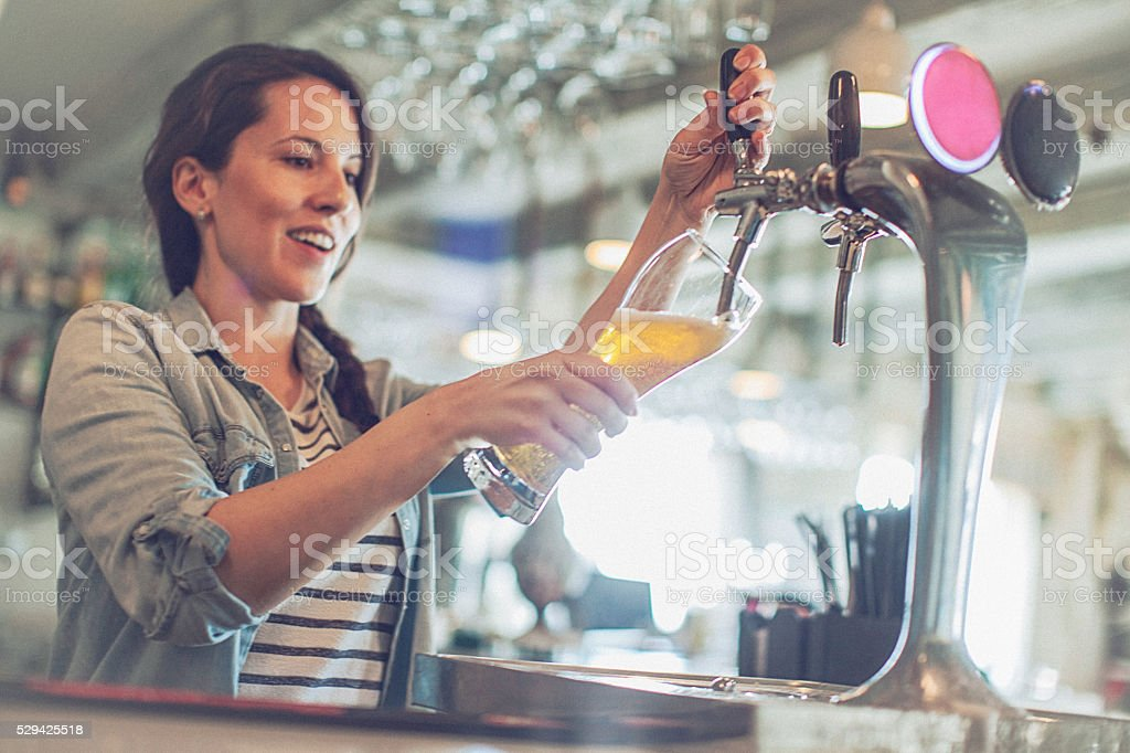 Casual young cheerful female bartender pouring beer from facet stock photo