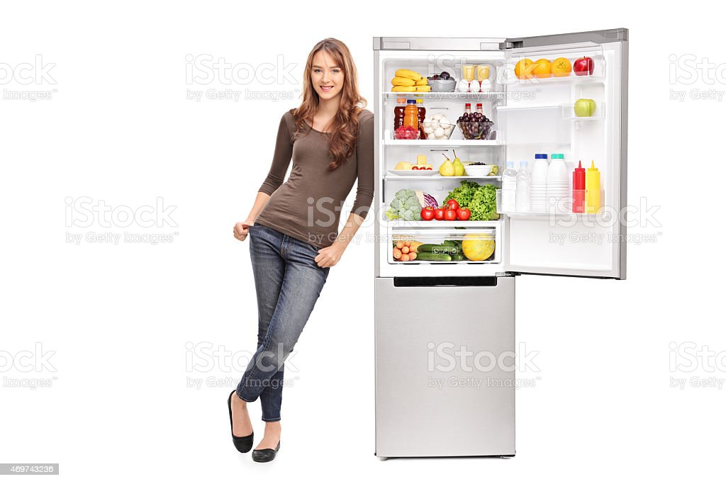 Casual young girl leaning on an opened refrigerator stock photo