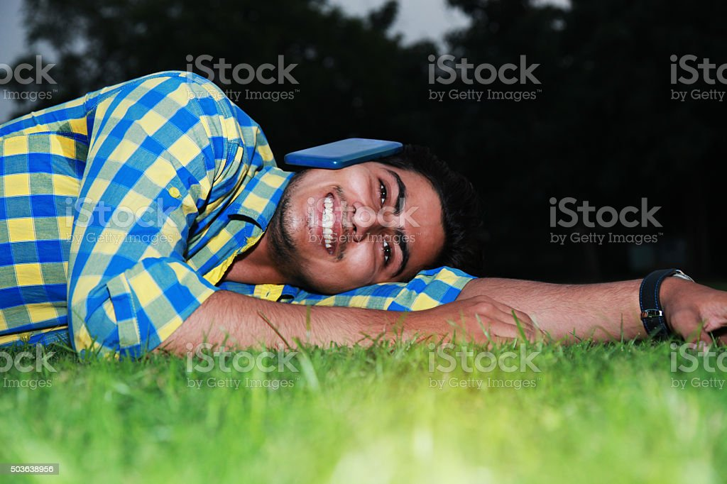Casual young man talking on phone in park stock photo
