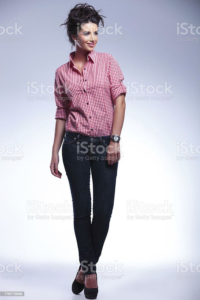 casual young woman in jeans and red shirt looking away royalty-free stock photo
