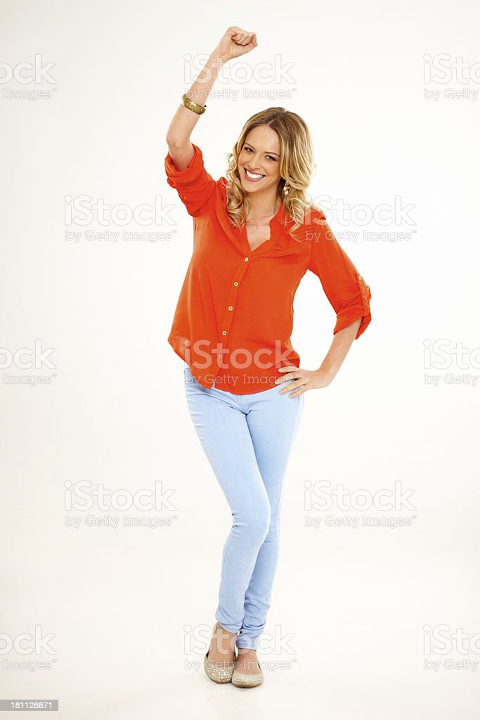 Casual young woman standing with her arm raised royalty-free stock photo