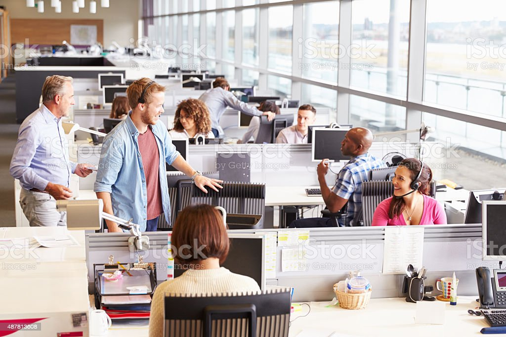 Casually dressed colleagues talking in an open plan office stock photo