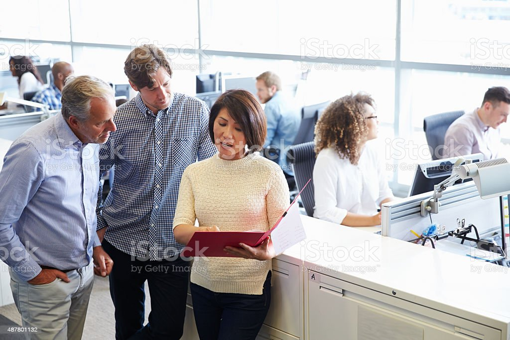 Casually dressed staff standing in a busy open plan office stock photo
