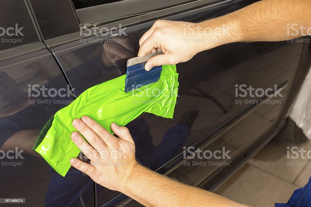 Cat wrapping specialist wraps a door handle with green foil stock photo