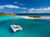 Catamaran at anchor in front of deserted island