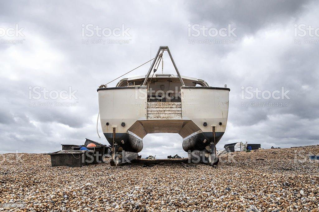 Catamaran boat standing on a rocky beach stock photo