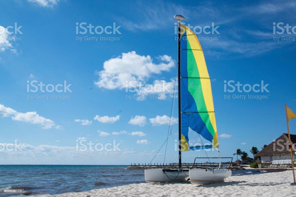Catamaran sailboat on white sand beach stock photo