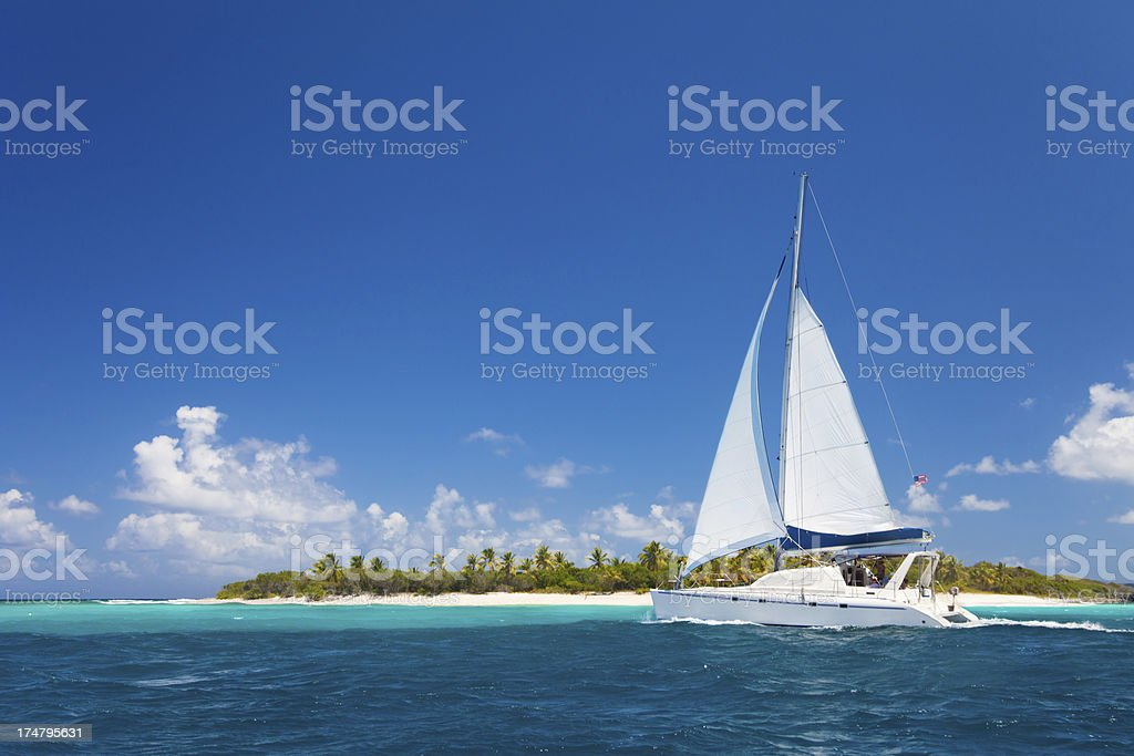 catamaran sailing close by a tropical island in the Caribbean stock photo