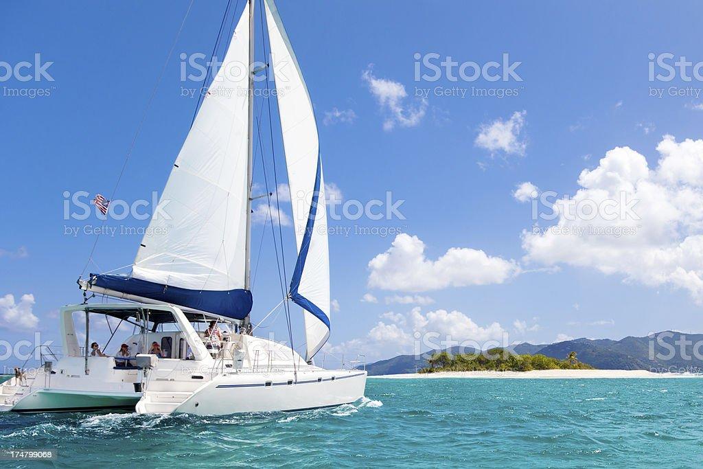 catamaran sailing close by a tropical island in the Caribbean stock photo