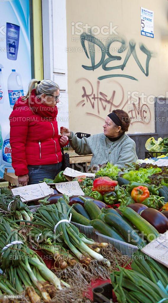 Catania, Sicily, Italy - November 30, 2016: A female veggie vendor...