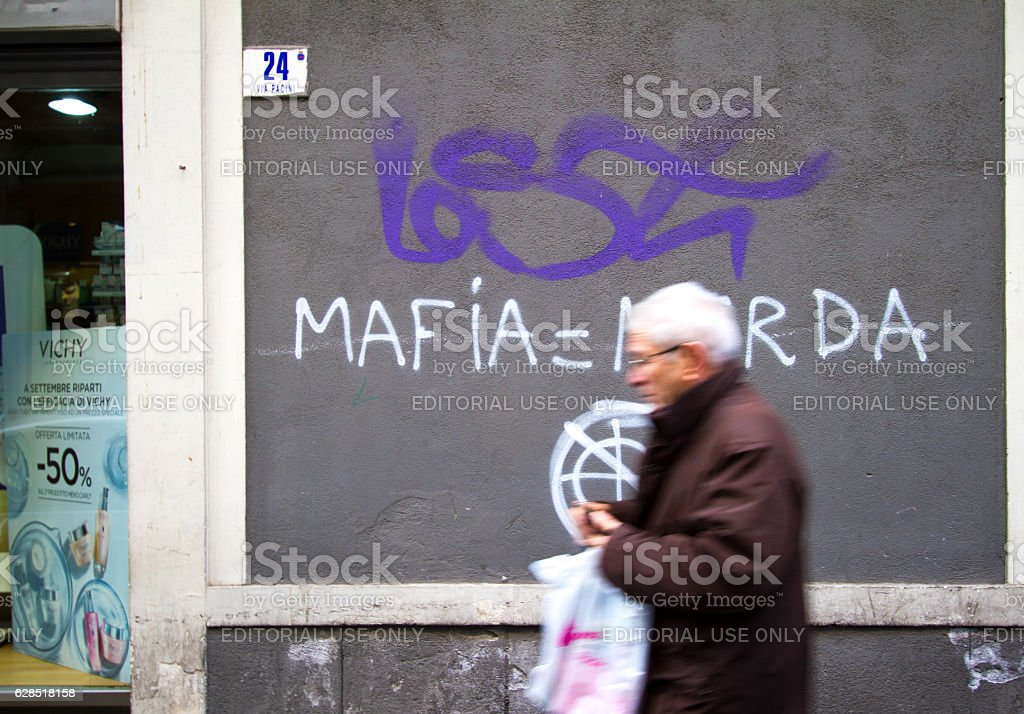 Catania, Sicily: Man Walks by Wall with Anti-Mafia Graffiti stock photo