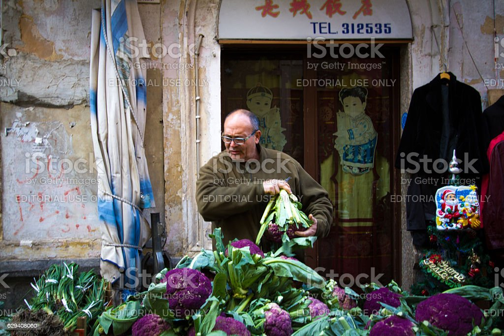 Catania, Sicily: Vendor with Purple Cauliflower at Outdoor Market stock photo