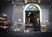 Catania, Sicily: Woman Emerges from Mini-Market, Veggie Crates, Bike