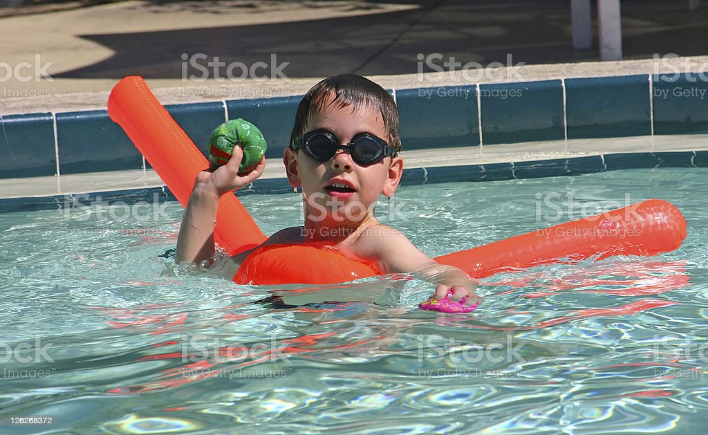 'Catch it!'  Young boy playing in the pool. royalty-free stock photo