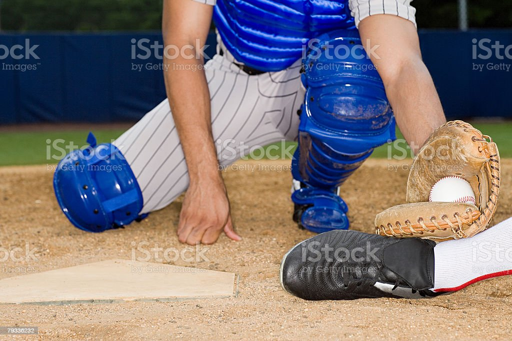 Catcher stopping player by home plate stock photo
