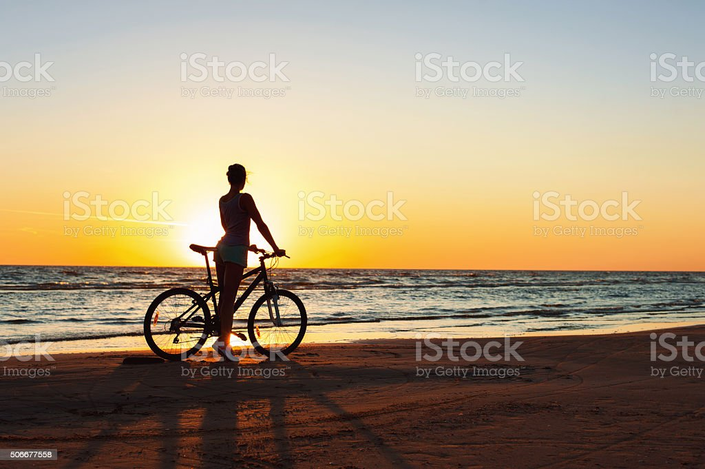 Catching a moment in time. Sporty woman cyclist at sunset stock photo