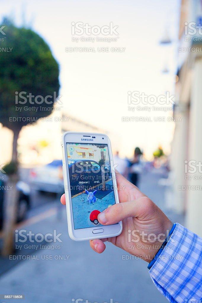Catching a Pokémon on Pokémon Go game in the street stock photo