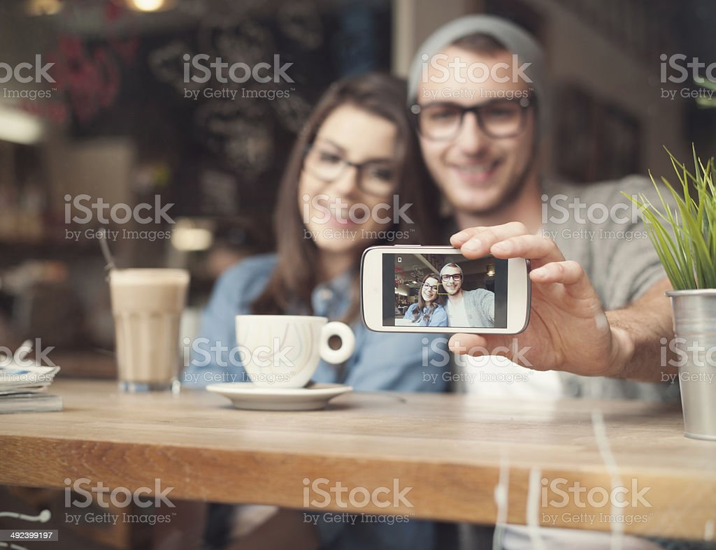 Catching memories by stylish young couple stock photo