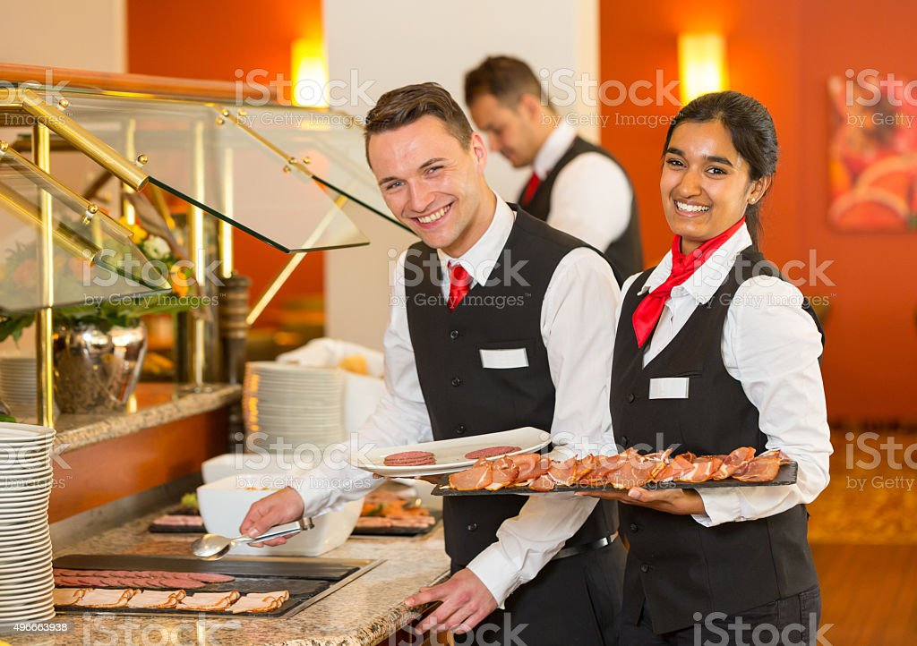 Catering service employees filling buffet at restaurant or hotel stock photo