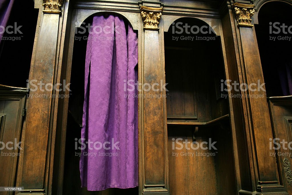 A Catholic confession booth with a purple curtain stock photo